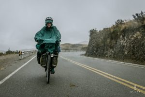 gringo cycling in the rain with rain cape