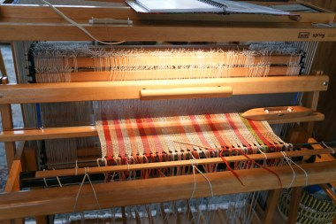 A floor loom with tea towels in orange, reds and creams tied onto the front.
