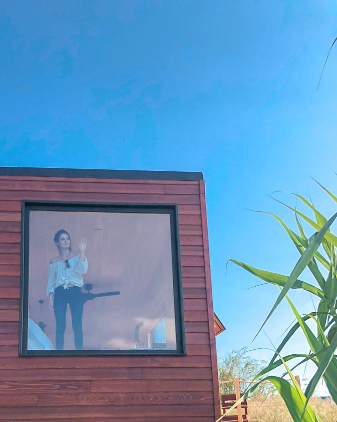 Woman in Tiny House from the Outside