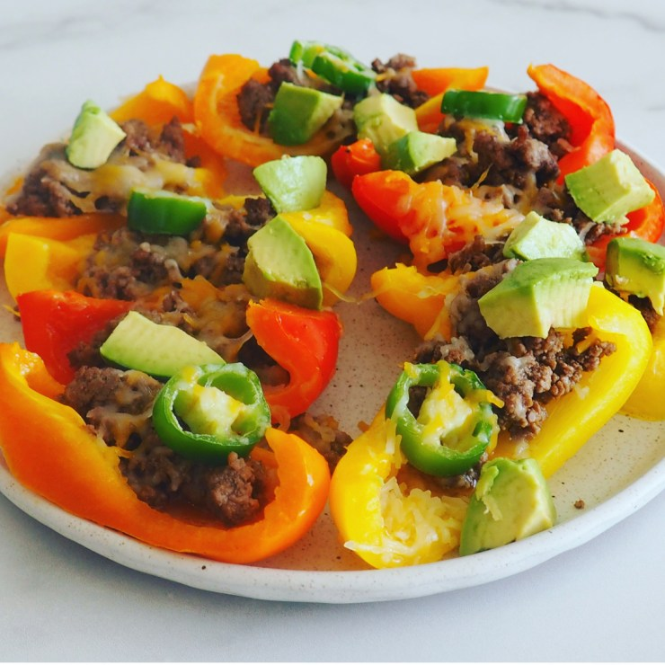 bell pepper nachos laying flat on a dish. bell peppers with ground beef, cheese, and avocado