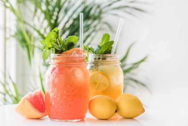 jars with delicious bright lemonades and straws on table
