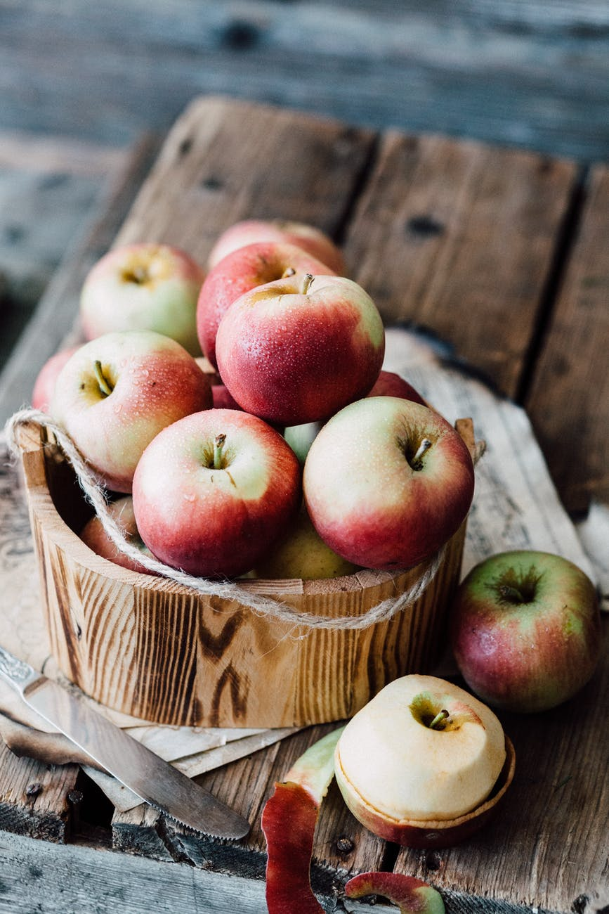 close up of apples in wooden bowl