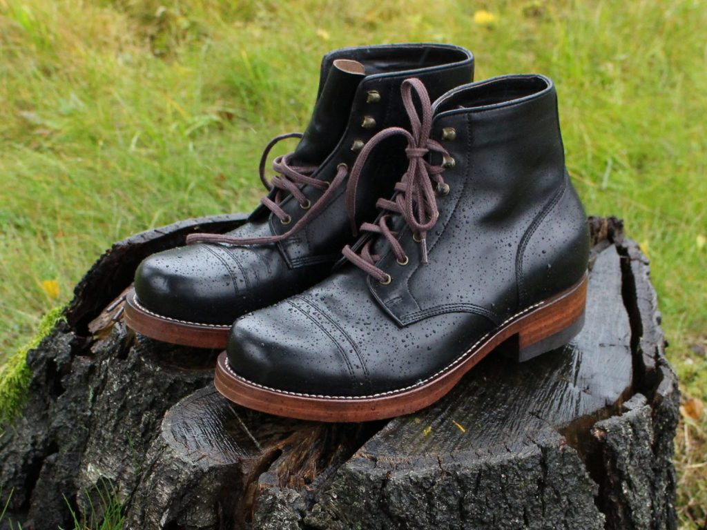 Jeansda Lancelot boots, ruggedly handsome in a light rain, on a tree stump in Norway.