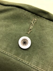Buttons and buttonholes are plentiful to allow for storm flap function on the army tent.