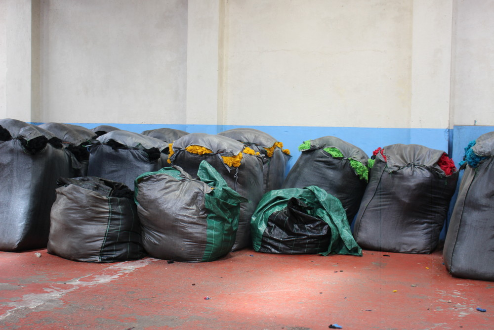 Big sacks of dyed wool ready for mixing. Notice the primary colours?