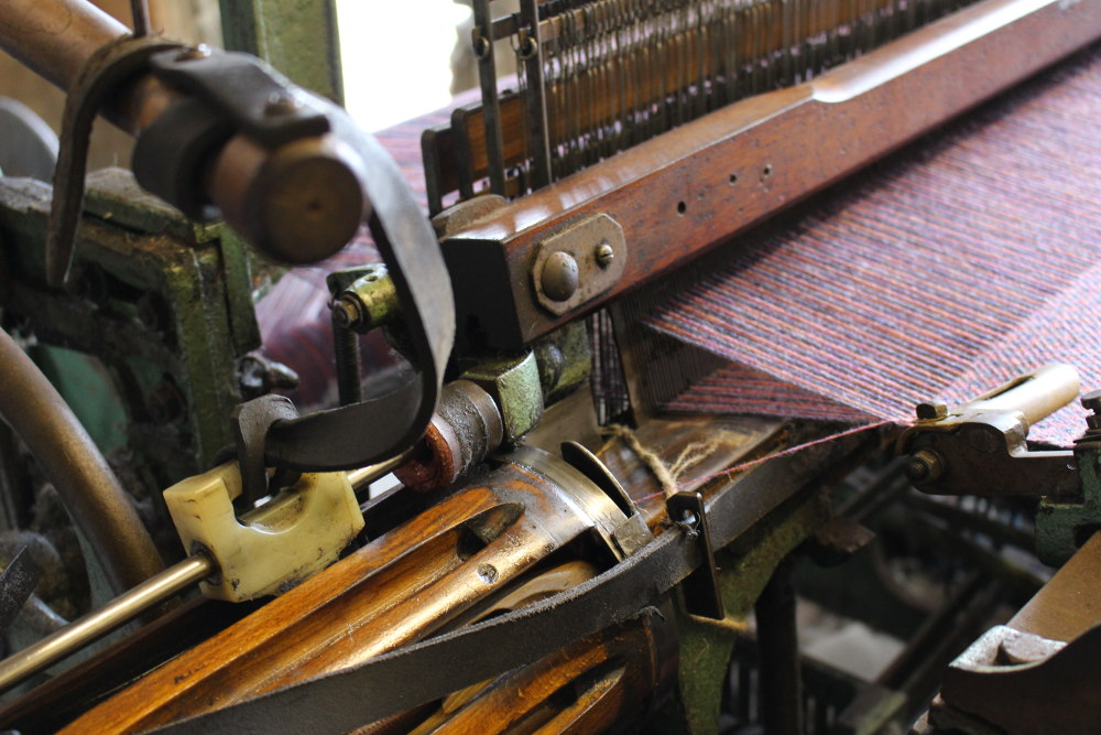 The business side of a Mk2 Hattersley loom, mid weaving. Blink and you'd miss the shuttle being whacked across from side to side!