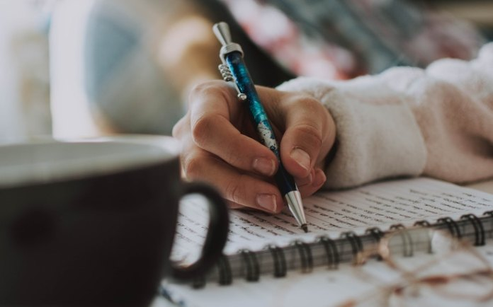 Woman writing poetry in her journal