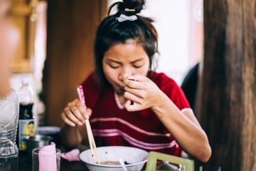 Person eating bowl of food with chopsticks and spoon