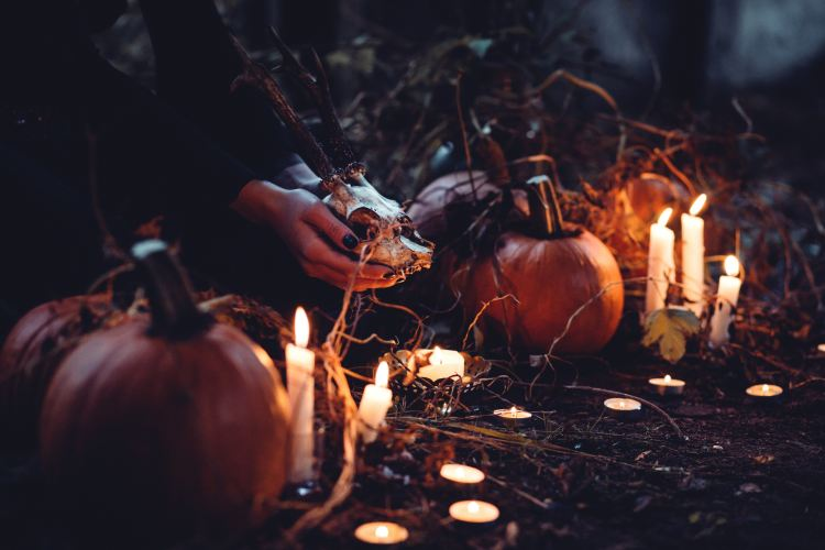 picture of person holding a skull, surrounded by pumpkins and candles in a dark outdoors space