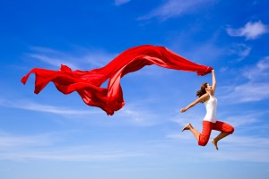 Happy woman leaping with red scarf