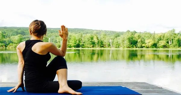 blog picture of woman doing yoga by lake