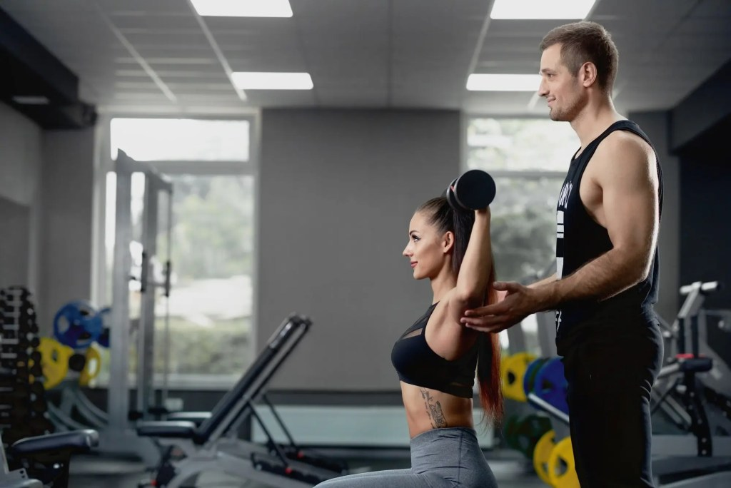 Male personal trainer helping woman working with heavy dumbbells at gym