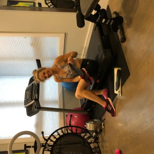 Girl sitting on treadmill, replacing shoe insole before running.