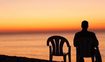 man and empty chair by lake