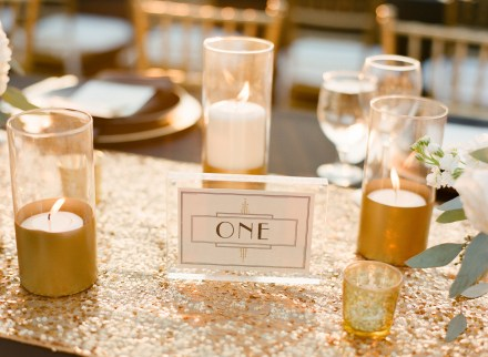 Gold sequinned table runners with candles in gold jars make a perfect table setting