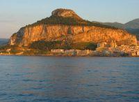 Die Stadt auf der Halbinsel ist in ein warmes Abendlicht getaucht. Im Hintergrund der Rocca di Cefalu.