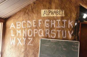 Im Klassenzimmer der Schule ist das Alphabet an die Wand gemalt.