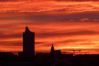 Der Sonnenaufgang taucht die Silhouette von Leipzig in zauberhafte Farben.