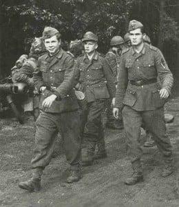 Deutsche Soldaten gehen unter Bewachung englischer Fallschirmjäger in Gefangenschaft