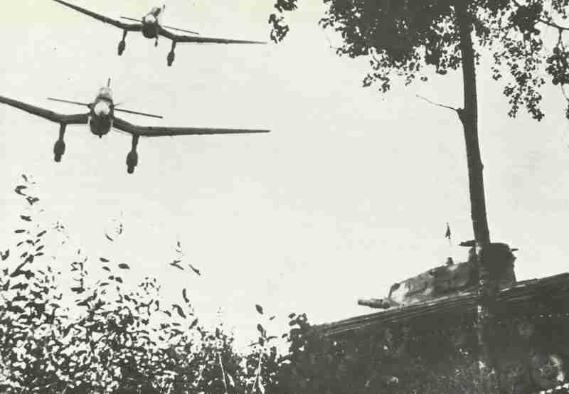 Stukas fliegen über einen PzKpfw IV hinweg.