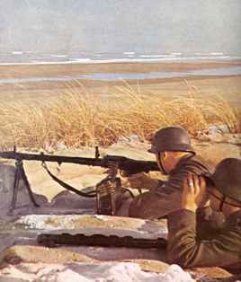 Soldaten bewachen mit ihrem MG34 einen Strand an der Kanal-Küste.