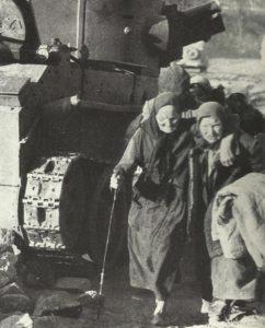 Flüchtlinge vor zerstörten russischen Panzer
