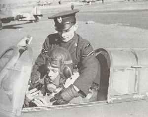 einem polnischen Piloten durch einen Unteroffizier der polnischen Luftwaffe in sein Flugzeug geholfen