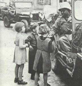 schwarzer US-Soldat gibt Süssigkeiten and Kinder ab