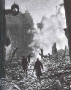 Einwohner Londons gehen morgens durch die noch qualmende Trümmer