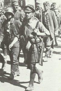 Soldat mit Hemdsärmeln, Shorts, Mütze und Wickelgamaschen