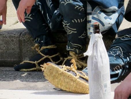 Traditionelle Strohsandalen und eine Flasche Sake.