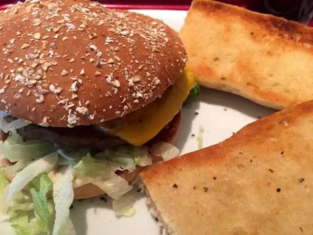 Cheeseburger und zwei Knoblauchbrote