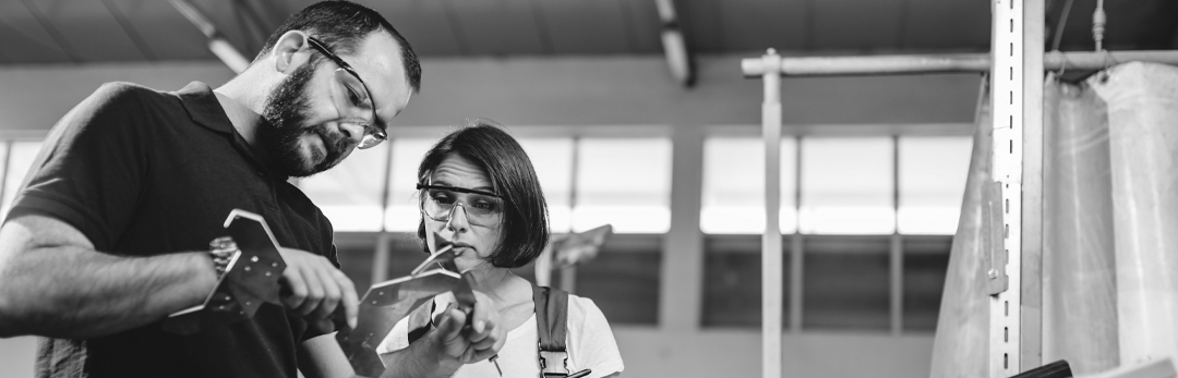 Man showing a woman how to use micrometer