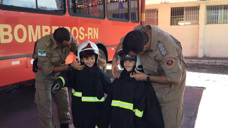 Bombeiros vestem roupas nas crianças