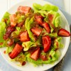 Flatlay of Spring Salad with Strawberry Balsamic Vinaigrette on a white plate with blue napkins