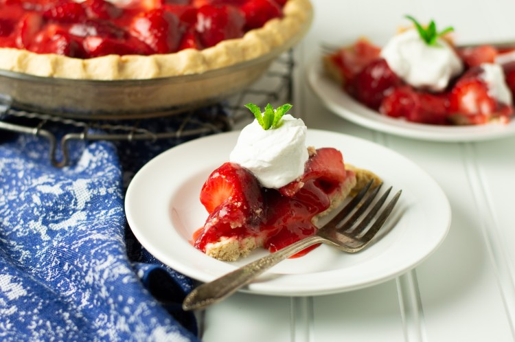 Fresh strawberry pie with whipped coconut cream garnished with a sprig of mint