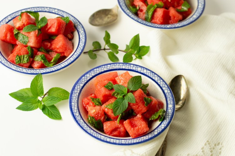 Three small bowls of cool watermelon with mint, tossed in a lime/avocado dressing