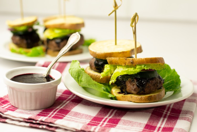 Bison sliders topped with zucchini slices, red onion, lettuce and blueberry BBQ sauce on white sweet potato slices