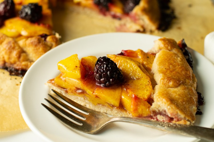 A slice of blackberry peach galette on a dessert plate, ready to nosh