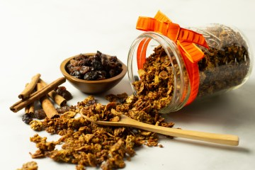 Crunchy Pumpkin Spice Granola tumbling out of a mason jar