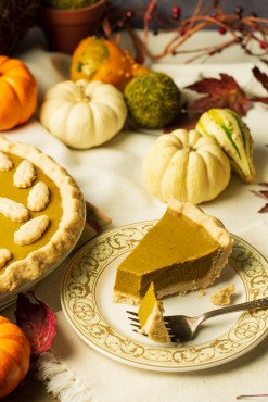 Closeup of a slice of pumpkin pie in a Thanksgiving scene