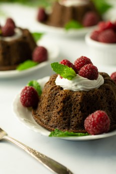 Closeup of Gingerbread Mini Bundt Cake, garnished with lemon cream, raspberries and mint