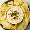 a bowl of AIP/Paleo Onion Dip on a plate full of crunchy cassava chips