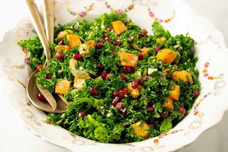 Massaged kale, roasted butternut squash and shallots, topped with pomegranate arils and dressed with a creamy tigernut dressing in a large salad bowl