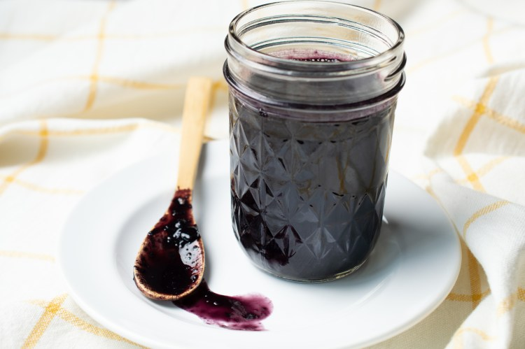 Blueberry BBQ Sauce in a glass jar on a plate with a wooden spoon nearby smearing the BBQ sauce