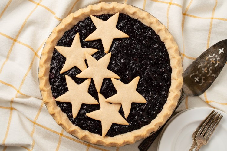 Flatlay of whole Blueberry Pie (AIP/Paleo) open face with stars cut from crust on top