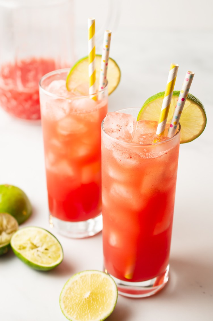Two tall glasses of Watermelon Limeade (AIP/Paleo) garnished with lime wheels and two patterned straws