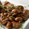 Roasted Balsamic Mushrooms (AIP/Paleo) on a rectangular platter with sprigs of fresh thyme