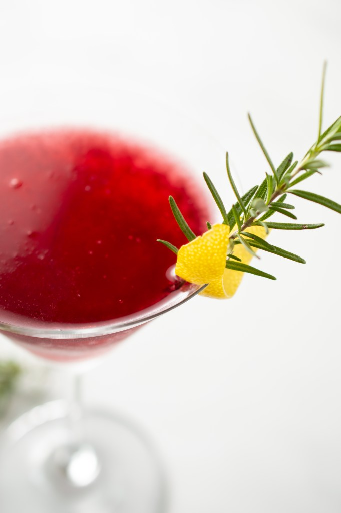 Closeup of the garnishes on a Pomegranate Rosemary Spritzer Mocktail in a martini glass