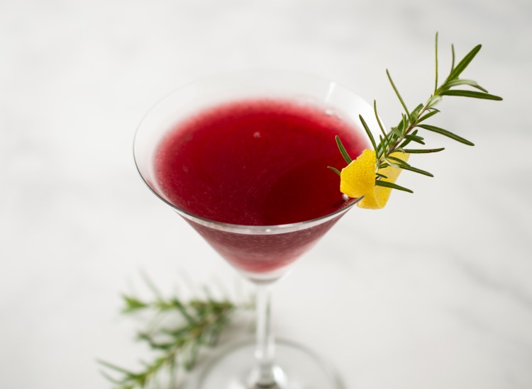 Pomegranate Rosemary Spritzer Mocktail wide view, garnished with a sprig of rosemary and a lemon twist
